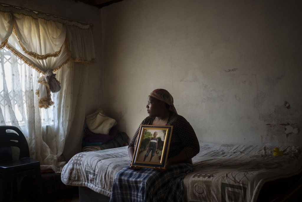 Rebecca Mohapi poses with a photograph in the bedroom of her son, 12-year-old Onthatile Mohapi, who mysteriously disappeared and was found dead a week...