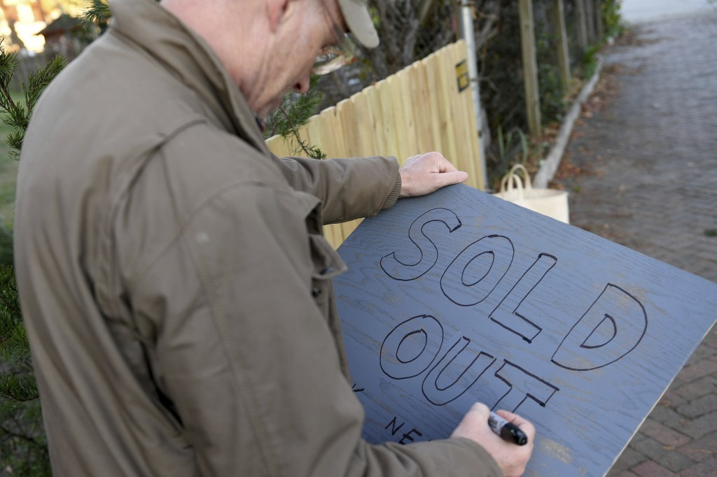 """Frank Pichel writes a sign reading """"Sold Out"""" after selling out of all of his trees, Sunday, Dec. 6, 2020, in Richmond, Va. The Virginia man has found..."""
