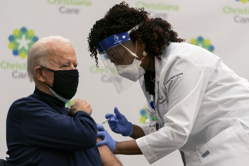 President-elect Joe Biden receives his first dose of the coronavirus vaccine from Nurse partitioner Tabe Mase at Christiana Hospital in Newark Del., M...