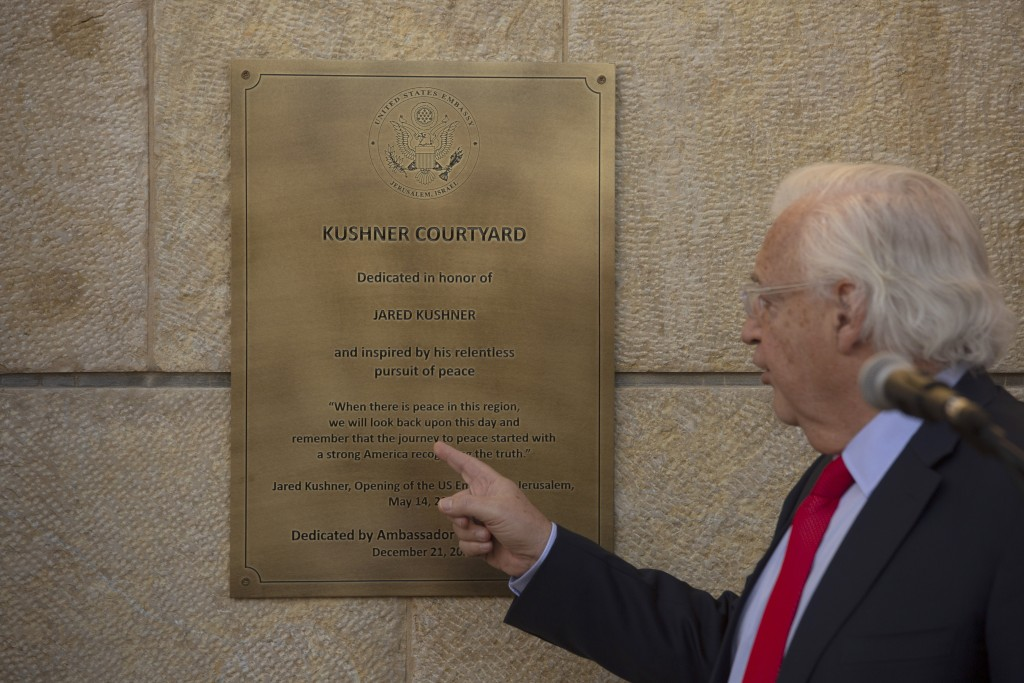 """U.S. Ambassador to Israel David Friedman, points to a plaque he unveiled  at the U.S. embassy in Jerusalem, designating it as the """"Kushner Courtyard,""""..."""