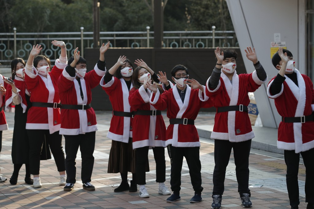 Volunteers wearing face masks wave after they load boxes onto a delivery truck during an event to send Christmas gifts for the underprivileged in Seou...