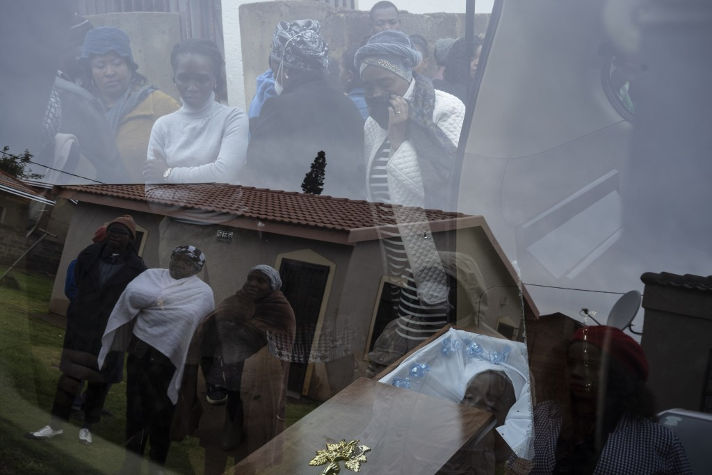 Mourners look at the body of 5-year-old Wandi Zitho at his funeral in Orange Farm, South Africa, on April 28, 2020. The boy was murdered in a suspecte...