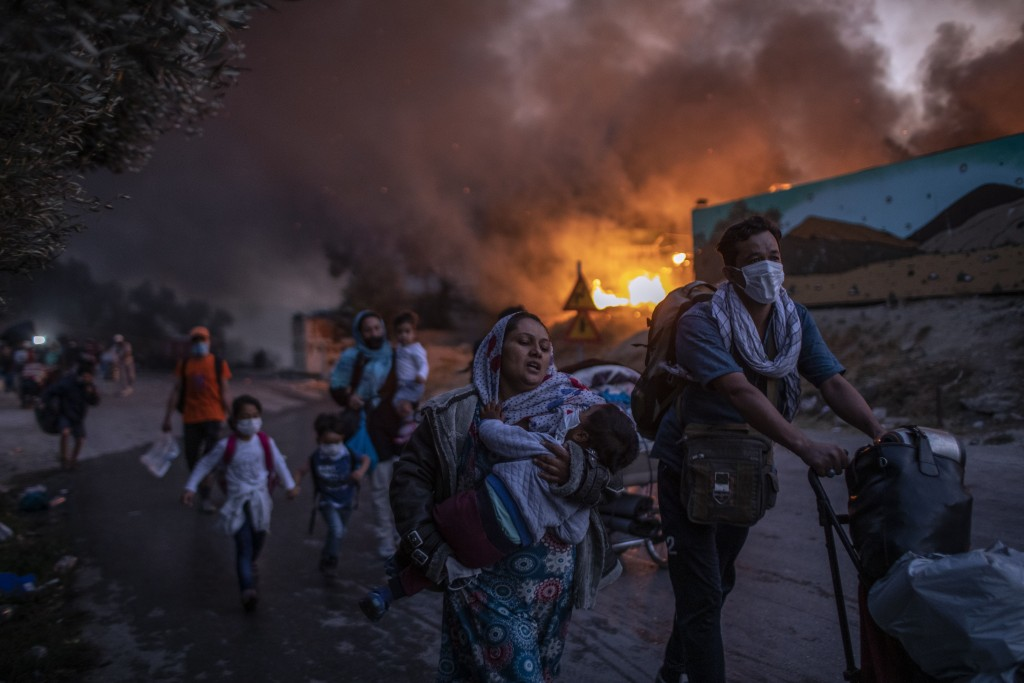 Refugees and migrants carrying their belongings flee a fire burning at Moria camp, on Lesbos island, Greece, Wednesday, Sept. 9, 2020. (AP Photo/Petro...