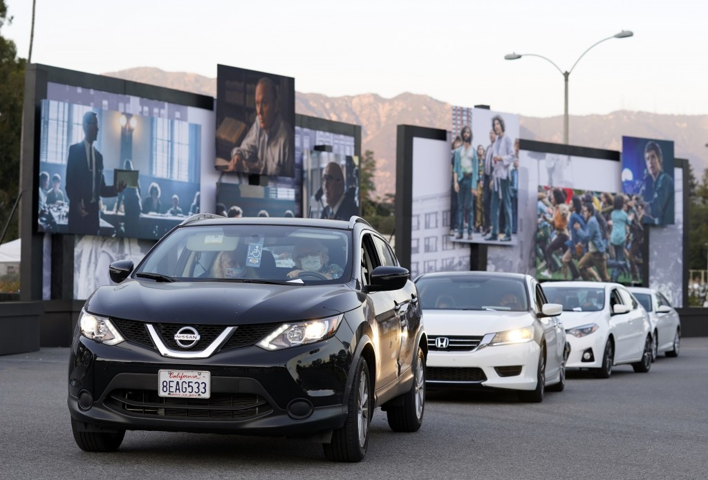 """FILE - Audience members in their cars drive past still photos from the Netflix film """"The Trial of the Chicago 7"""" at its drive-in premiere in Pasadena,..."""