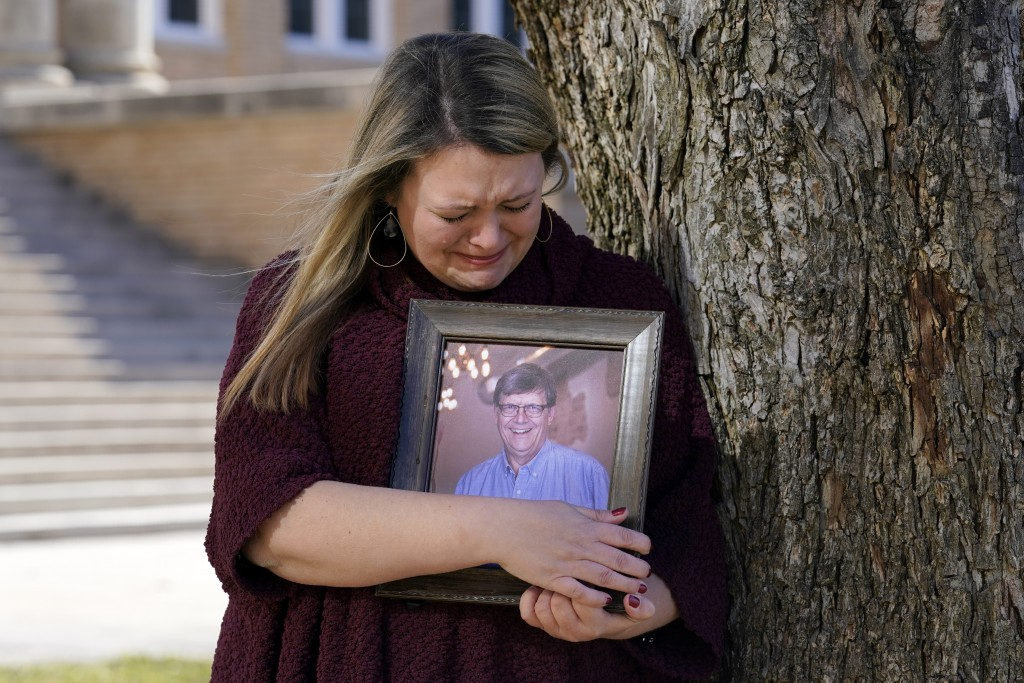 Katie Riggs Maxwell begins to cry as she hugs a portrait of her father Mark Riggs while posing for a photo, Wednesday, Dec. 16, 2020, on the campus of...
