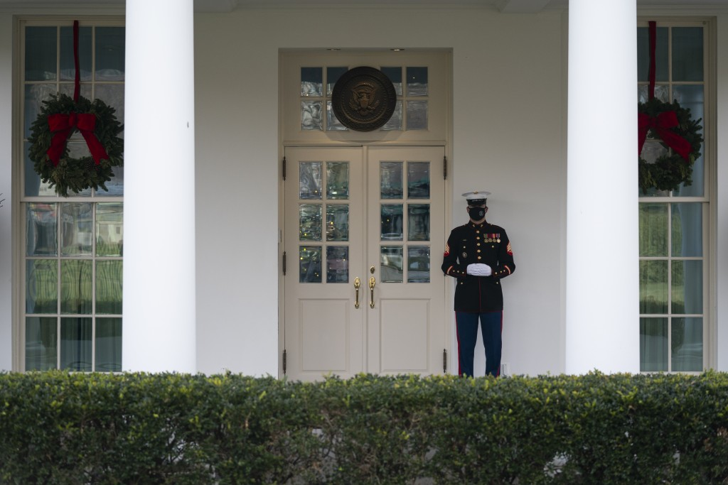 A Marine stands outside the entrance to the West Wing of the White House, signifying the President is in the Oval Office, Monday, Dec. 21, 2020, in Wa...