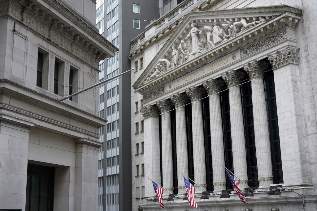 FILE - This Monday, Nov. 23, 2020 file photo shows the New York Stock Exchange, right, in New York. Stocks are drifting in mixed trading on Wall Stree...