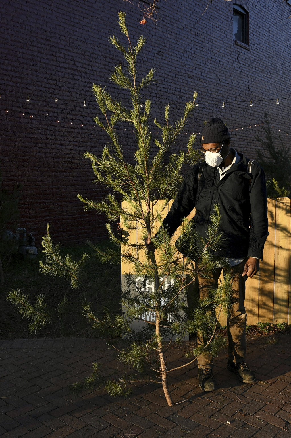 Brian Palmer, of Richmond, holds his recently purchased tree outside of Frank Pichel's tree lot, Sunday, Dec. 6, 2020, in Richmond, Va. A Virginia man...