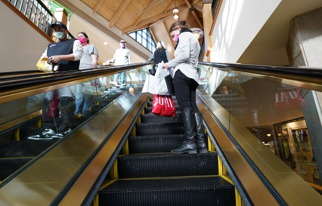 Holiday shoppers keep their distance and wear face masks while riding an escalator to battle the spread of the new coronavirus Tuesday, Dec. 8, 2020, ...