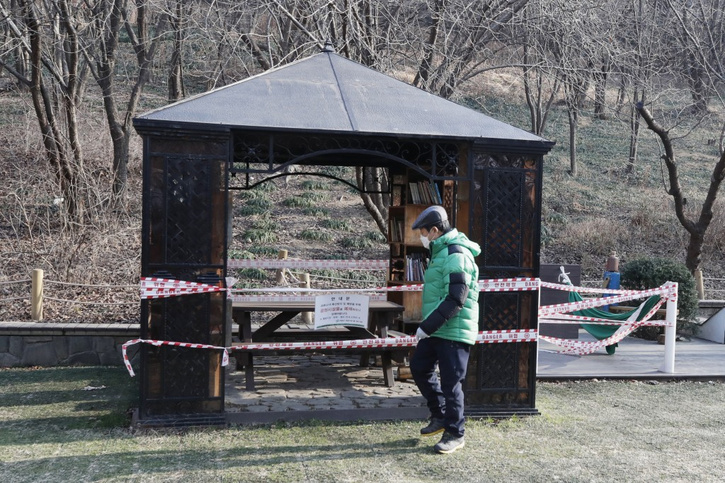 A man wearing a face mask walks past a rest area taped for social distancing and a precaution against the coronavirus in Seoul, South Korea, Tuesday, ...