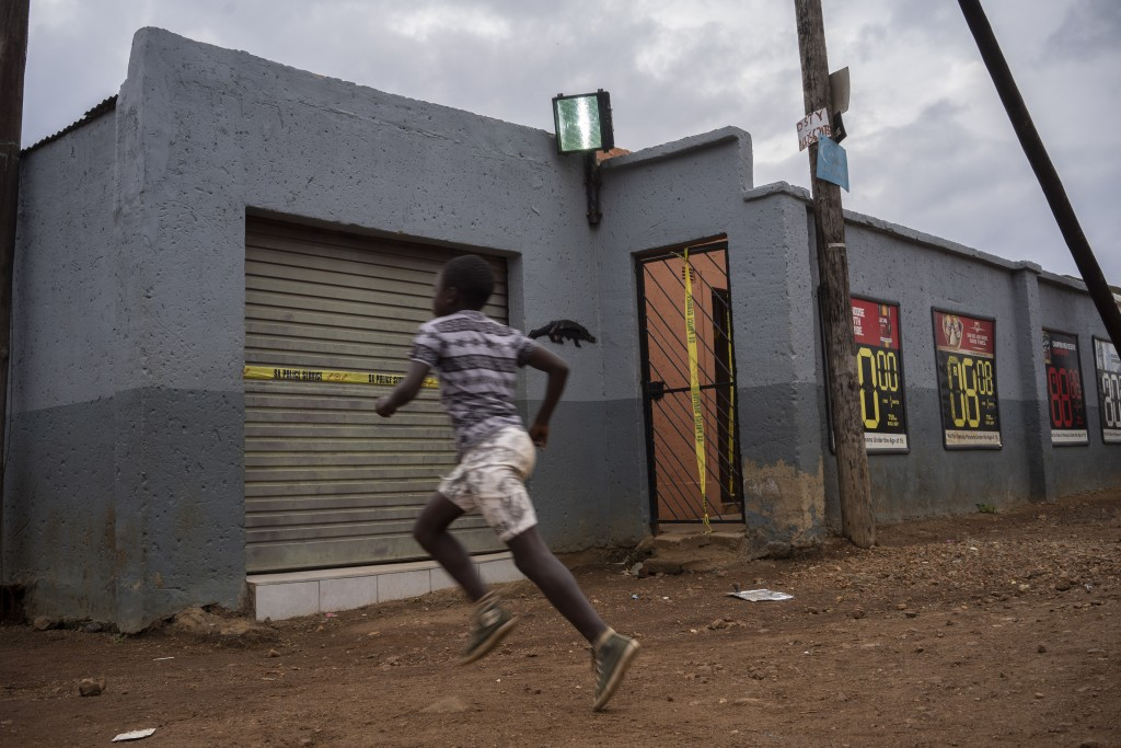 A boy runs past the tavern where the body of 5-year-old Wandi Zitho was found after he was murdered less than two weeks earlier in Orange Farm, South ...