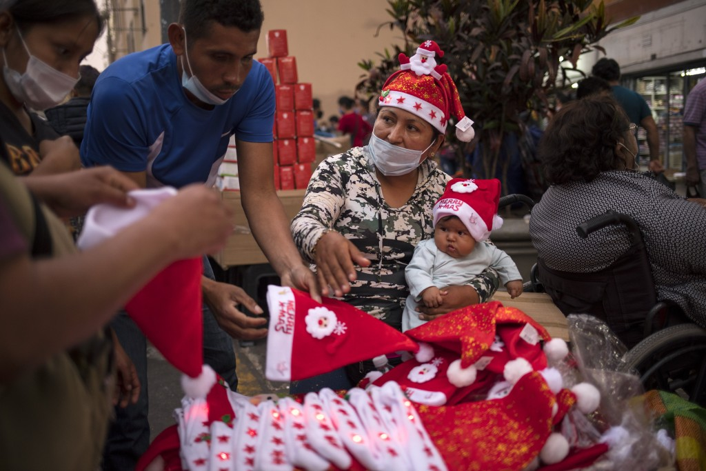 A woman sells Santa Claus hats while holding her baby at the Mesa Redonda Market, a popular spot for Christmas shopping, amid the COVID-19 pandemic in...