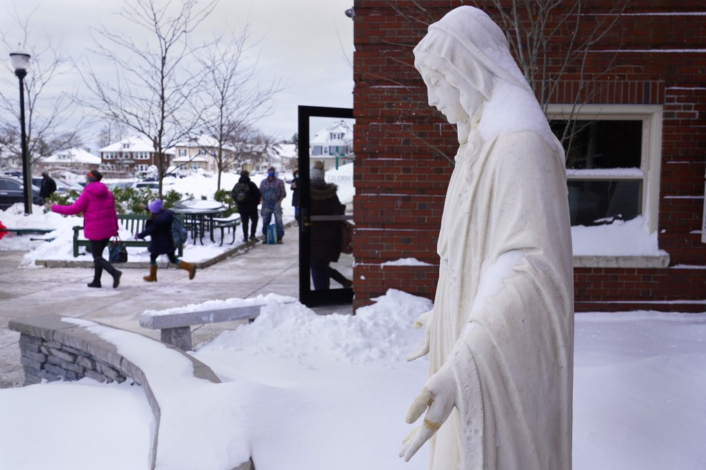 Students depart for their winter break, passing the statue of the Virgin Mary, outside the Saint Columbkille Partnership School, a Catholic school, Fr...