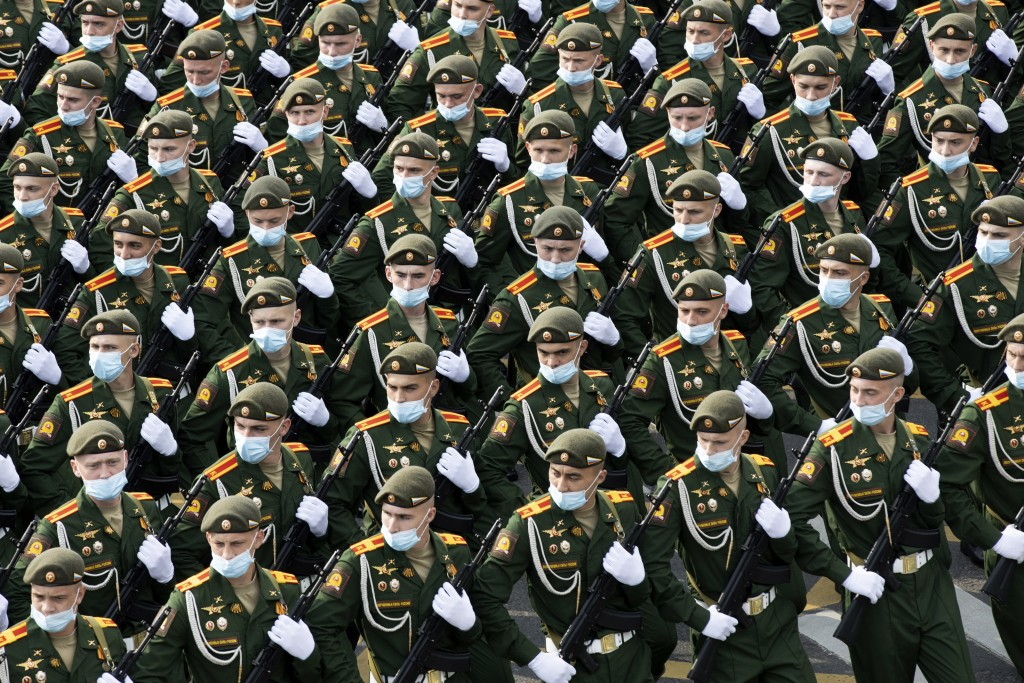 Russian soldiers wearing face masks to protect against coronavirus, march toward Red Square to attend a dress rehearsal for the Victory Day military p...