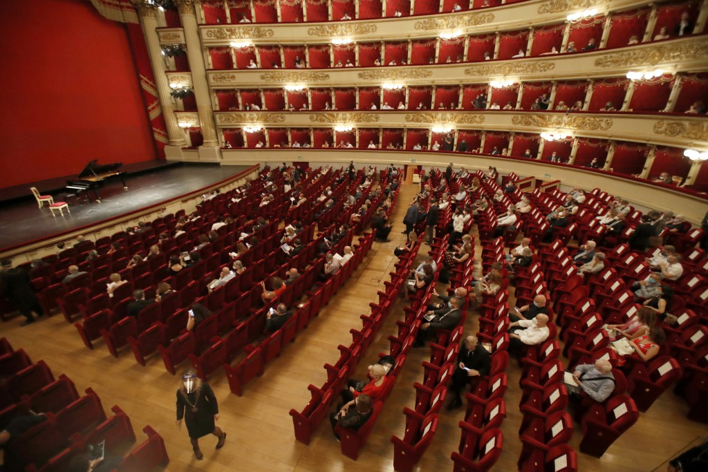 FILE - Spectators sit apart from each other to respect social distancing, prior to a show at the La Scala theater in Milan Italy, on July 6, 2020. La ...