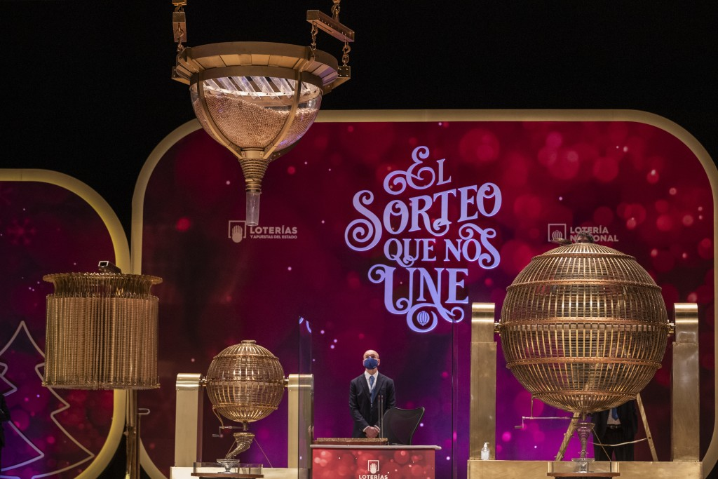 A worker observes the numbered lottery balls at Madrid's Teatro Real opera house during Spain's bumper Christmas lottery draw known as El Gordo, or Th...