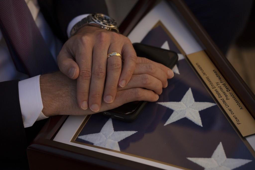 A staff member with U.S. White House Senior Adviser Jared Kushner holds a souvenir flag after U.S. Ambassador to Israel David Friedman, unveiled a pla...