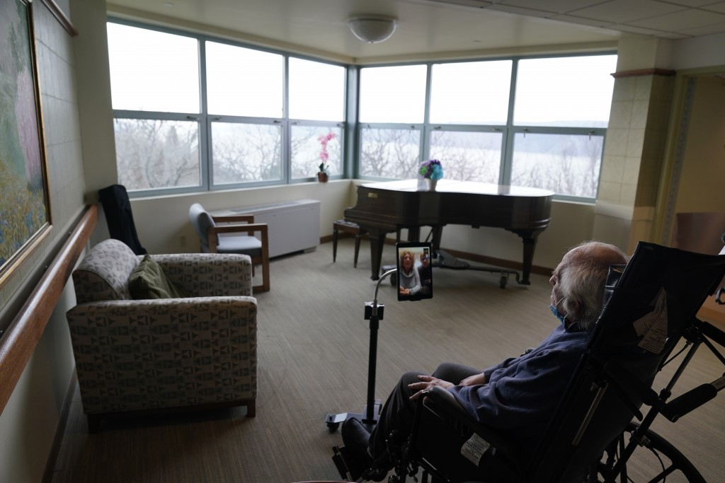 Jerry Woloz, 79, visits with family via a tablet at The Hebrew Home at Riverdale in New York, Wednesday, Dec. 9, 2020. Video and drive-by visits are t...