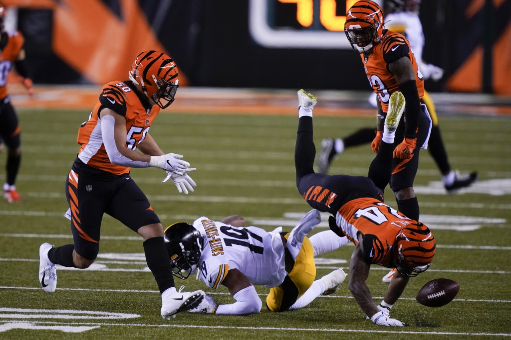 Cincinnati Bengals' Vonn Bell (24) and Jordan Evans (50) look to recover a fumble by Pittsburgh Steelers' JuJu Smith-Schuster (19) during the first ha...