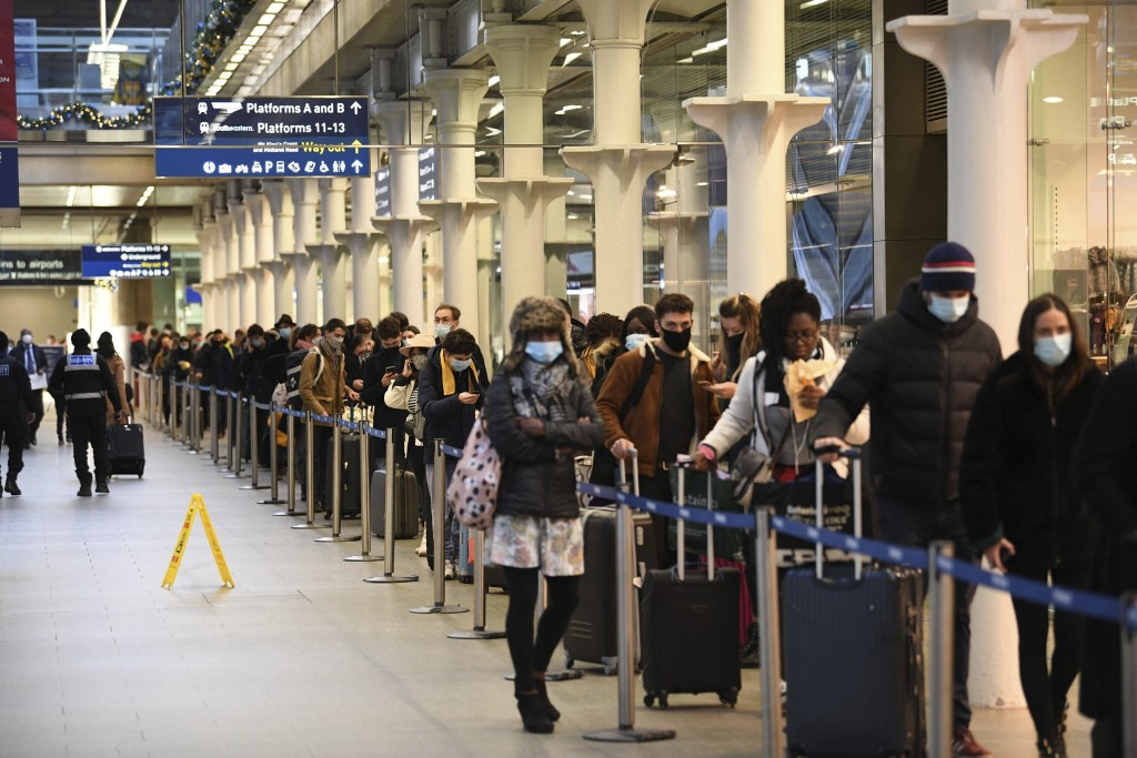 FILE - In this Sunday Dec. 20, 2020 file photo people at St Pancras station in London, wait to board the last train to Paris today. Instead of Christm...