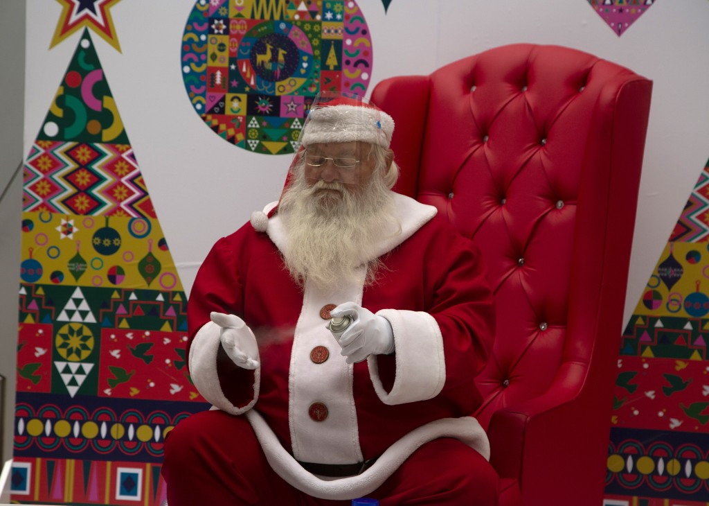 FILE - In this Tuesday, Dec. 22, 2020 file photo a man dressed as Santa Claus sanitizes his gloved hands, to protect against COVID-19, during a day of...