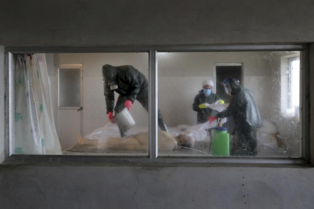 Hassan Khabir, 31, left, Ali Rahimi 53, center, and Mohammad Hossein Khoshnazar, 18, volunteer clerics wearing protective clothing prepare the body of...