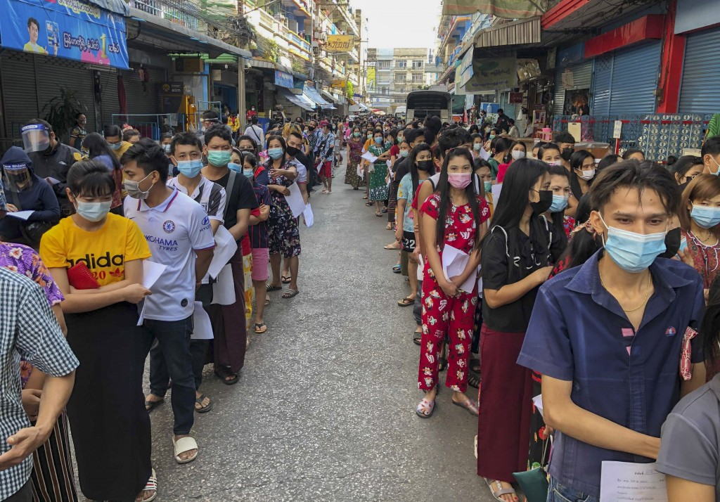 FILE - In this Dec. 20, 2020, file photo,  People stand in lines to get COVID-19 tests in Samut Sakhon, South of Bangkok. Thailand, which has kept the...