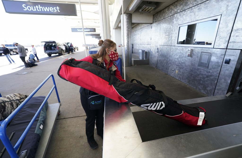 A baggage handler places a bag containing skis on a conveyor belt to be checked in by a traveler at the Southwest Airlines ticket counter in the main ...