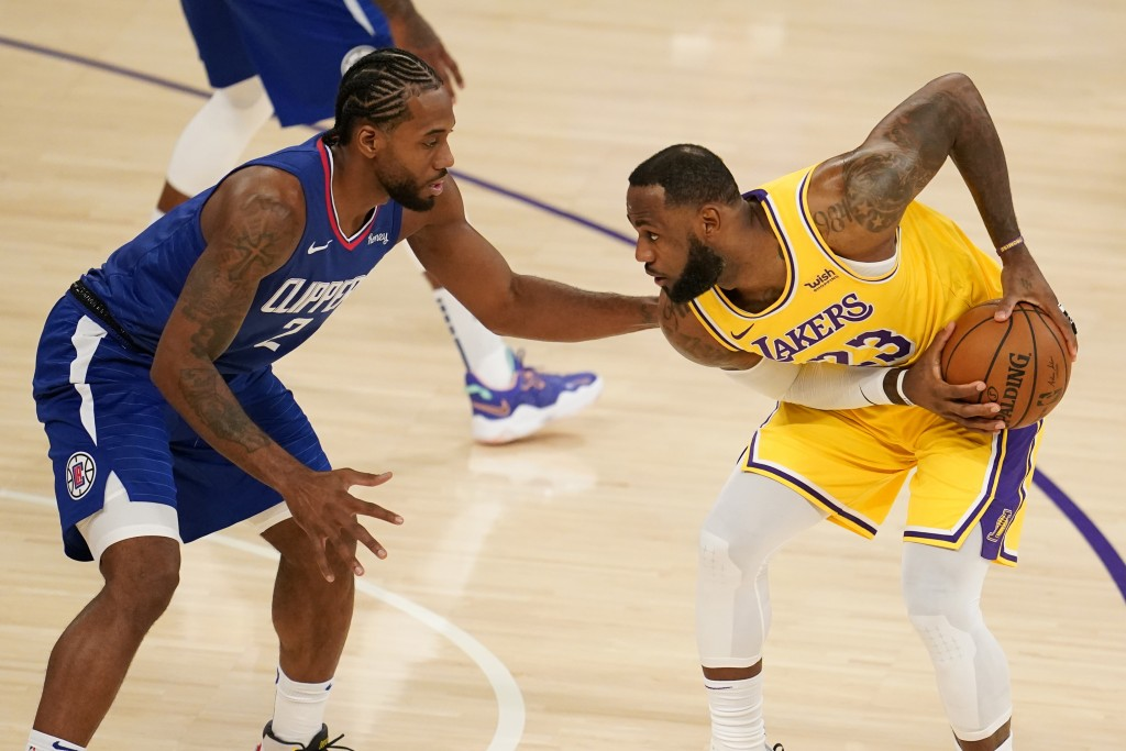 Los Angeles Lakers forward LeBron James, right, is defended by Los Angeles Clippers forward Kawhi Leonard during the first half of an NBA basketball g...