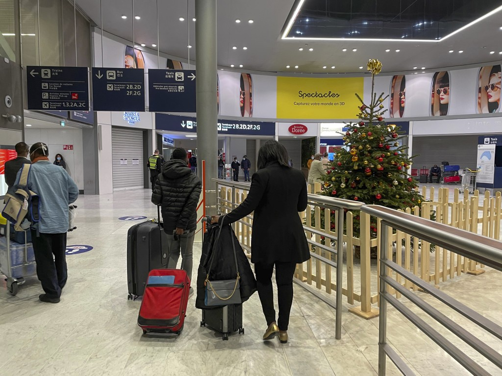 Arriving passengers walk by a Christmas tree at Paris Charles de Gaulle airport terminal E Tuesday Dec. 22, 2020. More and more countries around the w...