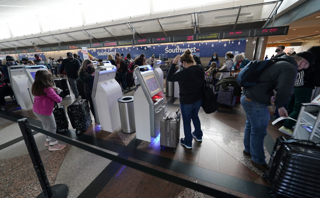 Travellers wear face masks while using the self-checking kiosks at the Southwest Airlines ticket counter in the main terminal of Denver International ...