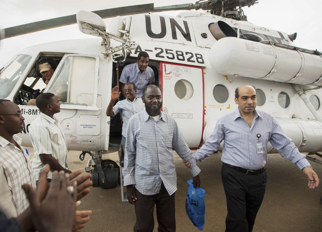 FILE - In this July 19, 2014 file photo, a member of the joint U.N. African Union Mission in Darfur (UNAMID), right, escorts three freed humanitarian ...