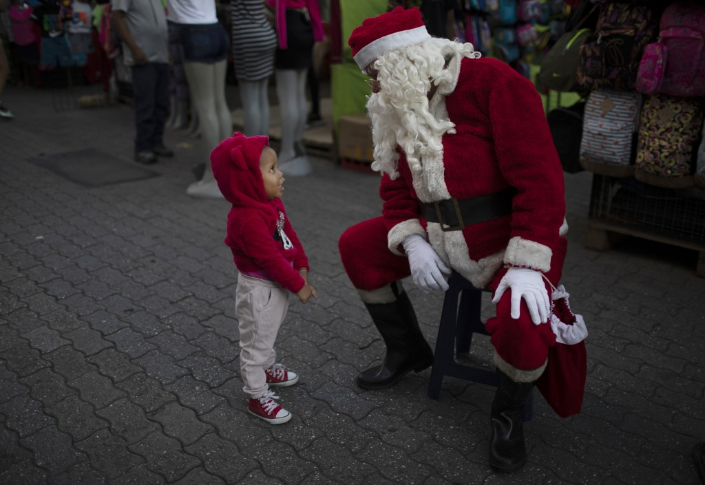 FILE - In this Dec. 18, 2020, file photo, Fredy Parra, dressed as Santa Claus, speaks to a girl at a Christmas fair in Caracas, Venezuela. For more th...
