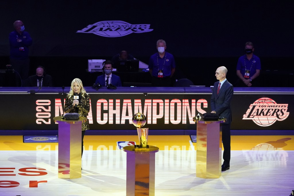 Los Angeles Lakers owner Jeanie Buss, left, speaks behind the championship trophy, near NBA Commissioner Adam Silver before the team's basketball game...