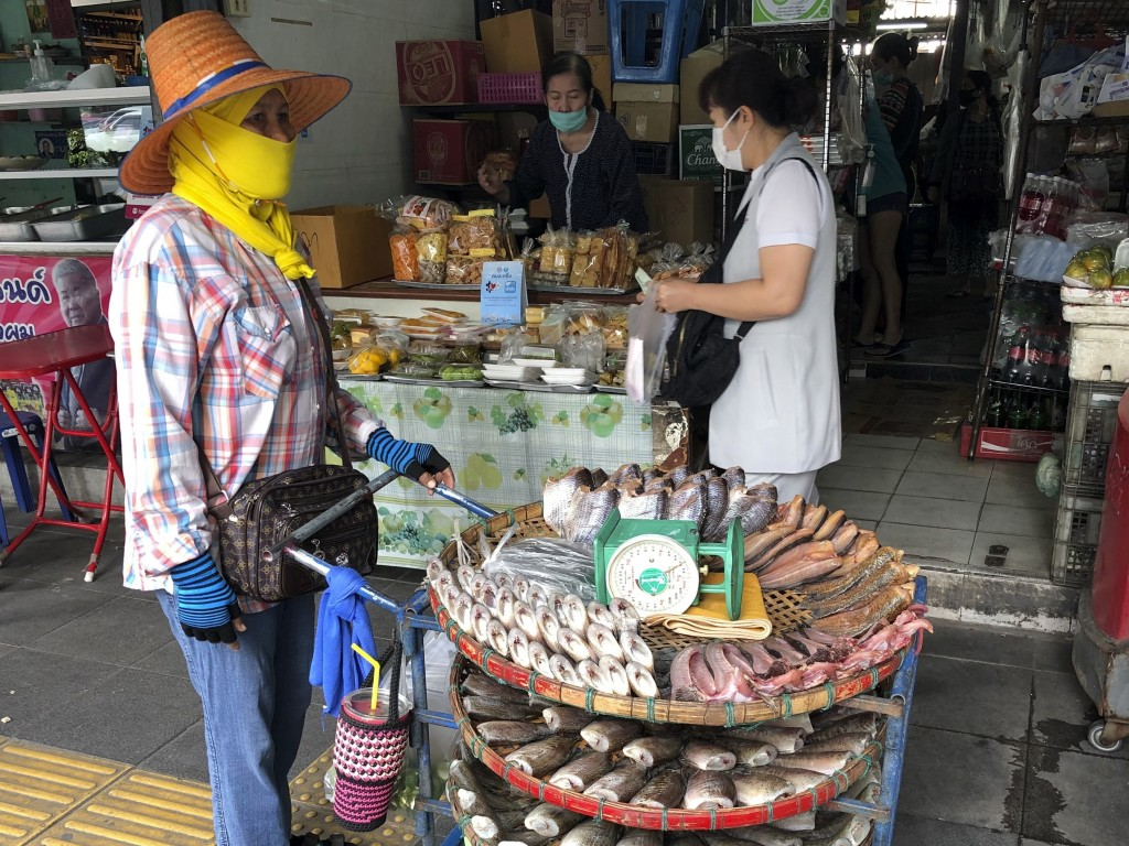 A vendor wearing a face covering to help prevent the spread of coronavirus sells fish from a pushcart outside a produce market in central Bangkok on W...