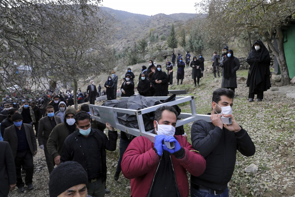 Mourners carry the body of Keyumars Ziaee 60, who died from COVID-19 at a cemetery in the Shir Kola village on the outskirts of the city of Ghaemshahr...