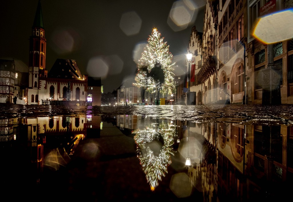 FILE - In this Dec. 20, 2020, file photo, people walk past the Christmas tree in the Roemerberg square that is reflected in a puddle in Frankfurt, Ger...