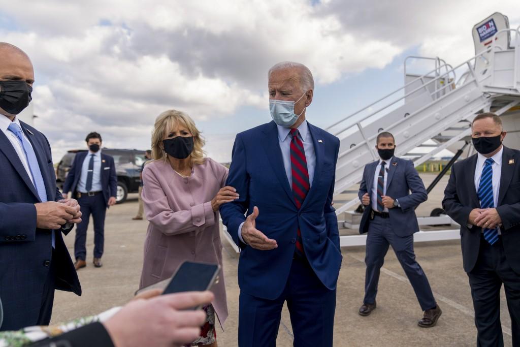 Jill Biden moves her husband, Democratic presidential candidate former Vice President Joe Biden, back from members of the media as he speaks outside h...