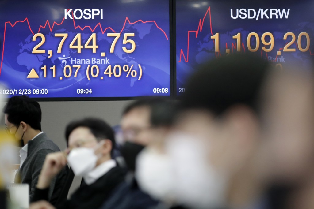 The Korea Composite Stock Price Index (KOSPI), left, and the foreign exchange rate between U.S. dollar and South Korean won are displayed at the scree...