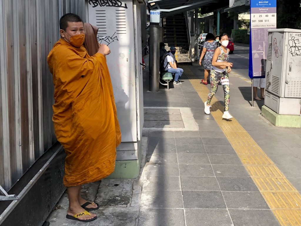 A Buddhist monk wearing a face covering to help prevent the spread of coronavirus waits for a bus along Sukhumvit Road in Bangkok on Wednesday, Dec. 2...