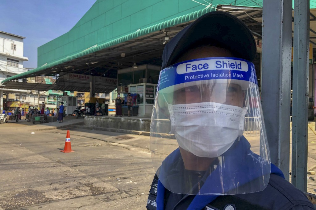 FILE - In this Dec. 20, 2020, file photo, a guard with a face-shield stands near a shrimp market in Samut Sakhon, south of Bangkok. Thailand, which ha...