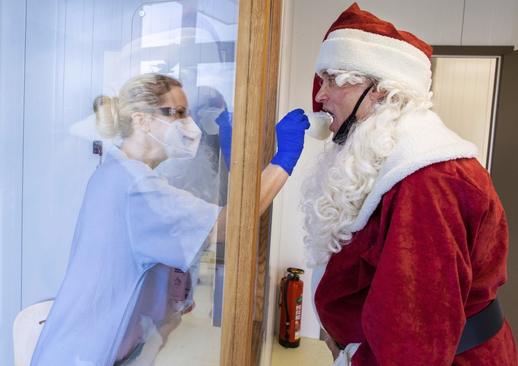 FILE - In this Dec. 21, 2020, file photo, Tessa Boulton, left, takes a swab test from Michael Kruse, dressed as Santa Claus, at a coronavirus testing ...