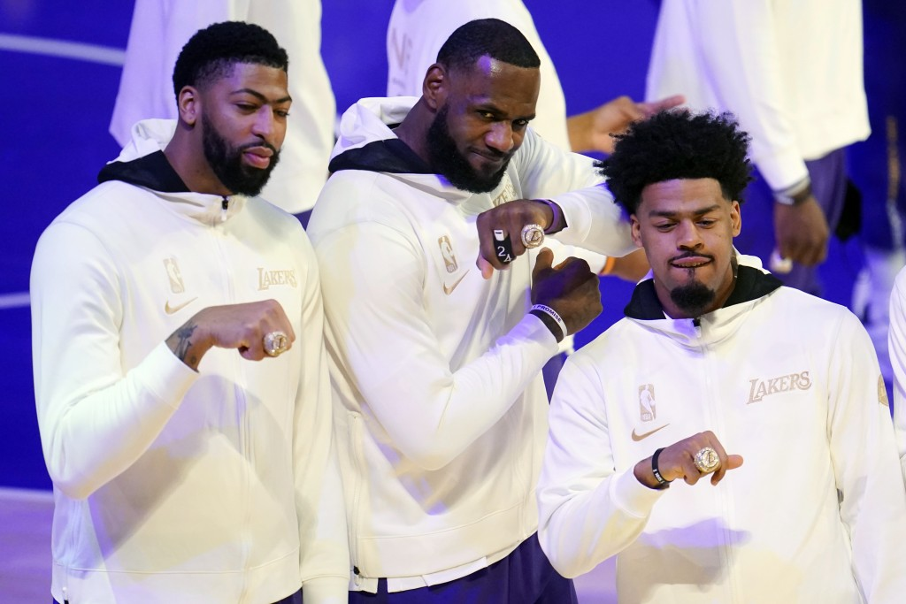 Los Angeles Lakers' Anthony Davis, left, LeBron James, center, and Quinn Cook show their championship rings before the team's NBA basketball game agai...