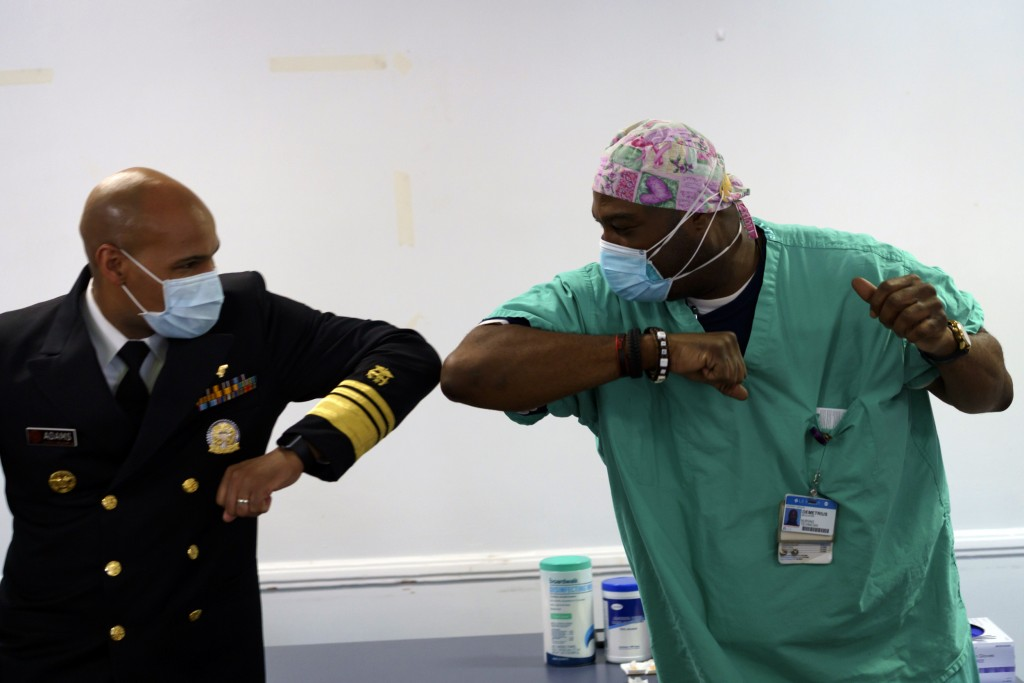 Surgeon General of the U.S. Jerome Adams, left, elbow-bumps Emergency Room technician Demetrius Mcalister after Mcalister got the Pfizer COVID-19 vacc...