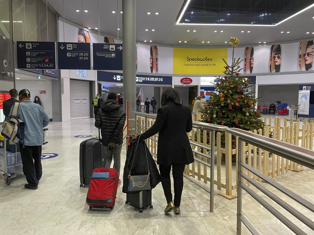 FILE - In this Dec. 22, 2020, file photo, passengers walk by a Christmas tree at Paris Charles de Gaulle airport terminal E. All most people wanted fo...