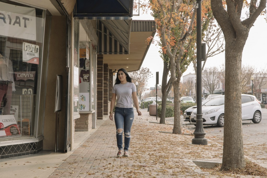 Alexandra Orozco walks down the main street of Delano, Calif., on Sunday, Dec. 6, 2020. Just over a two-hour drive from Los Angeles, the population of...