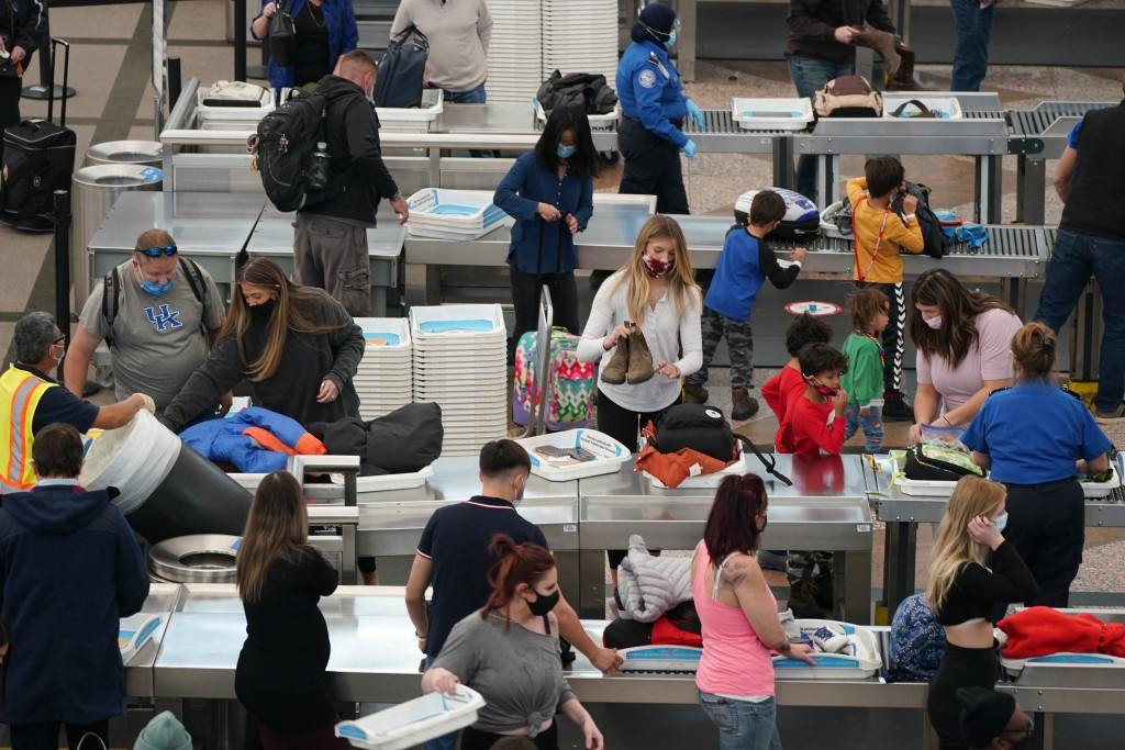 Travelers wear face masks while passing through the south security checkpoint in the main terminal of Denver International Airport Tuesday, Dec. 22, 2...