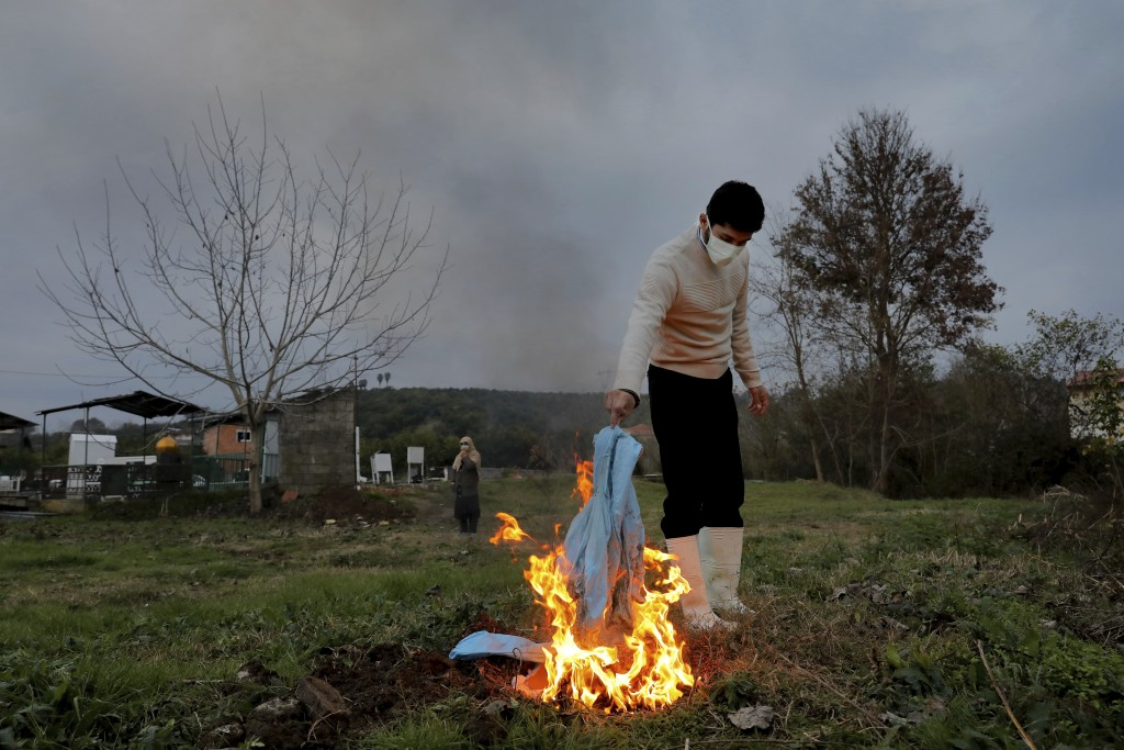 Mohammad Hossein Khoshnazar, 18, a cleric volunteer burns his protective clothes after the funeral of Ghorbanali Mahmoudi, 59, who died from COVID-19 ...