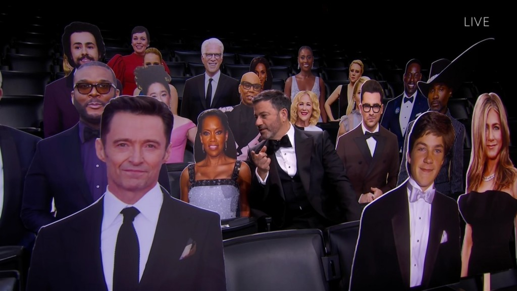 This image released by the Television Academy shows host Jimmy Kimmel, center, chatting with a cardboard cut-out of Regina King while surrounded by ot...