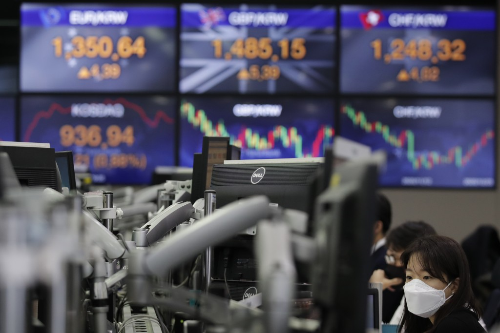 A currency trader watches computer monitors near the screens showing the foreign exchange rates at the foreign exchange dealing room in Seoul, South K...